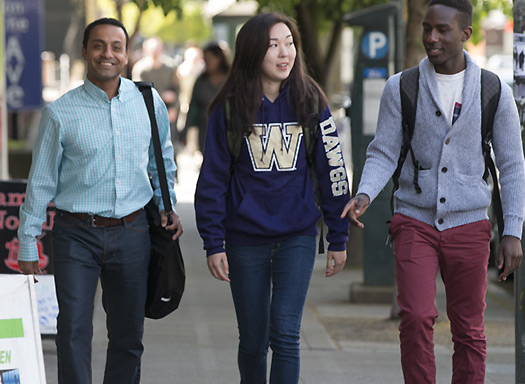 two young men and young woman walking along sidewalk