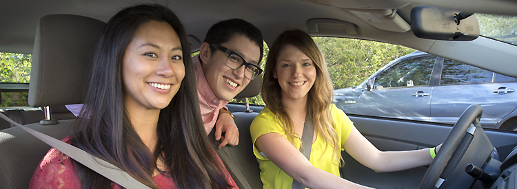 three students in a car carpooling