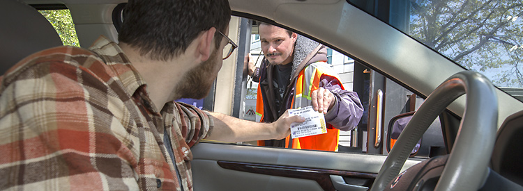 driver in car receiving parking permit from a gatehouse staff person