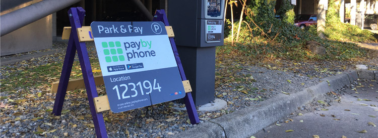pay by phone sign near a parking pay machine in padelford parking lot