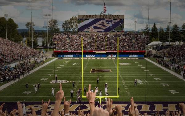 football game at husky stadium with fans raising their hands in the foreground